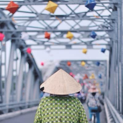 Vietnamese lady in her conical hat passing the bridge on her bicycle in the imperial city of Hue, Vietnam