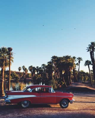 Vintage Chevrolet Bel Air surrounded by palm trees and a lagoon.