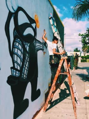 LA Artist JaQ Dutch working on a mural in West Adams.