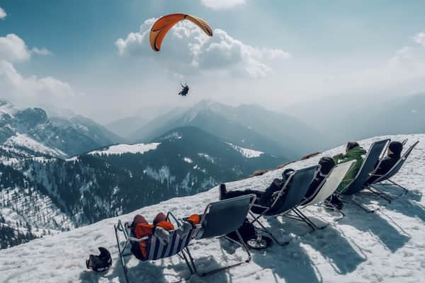 Skiers relaxing in winter mountain scenery with paraglider flying over them.