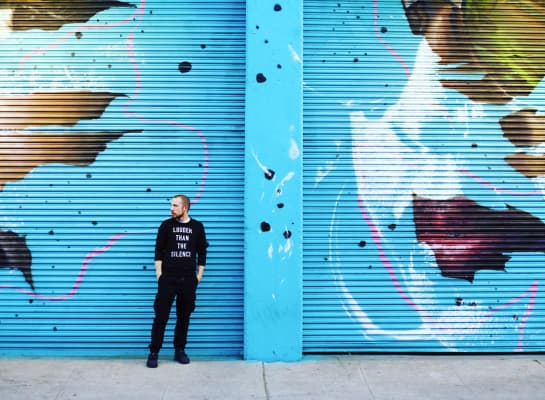 Blue city graffiti art with young man in black