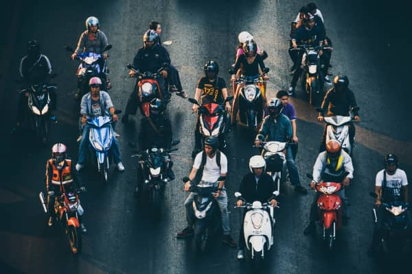 Motorcyclists wait at a busy junction during a rainy rush hour.