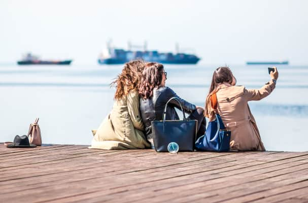 Young Girls Friends Taking Selfie With Mobile Phone At The Dock