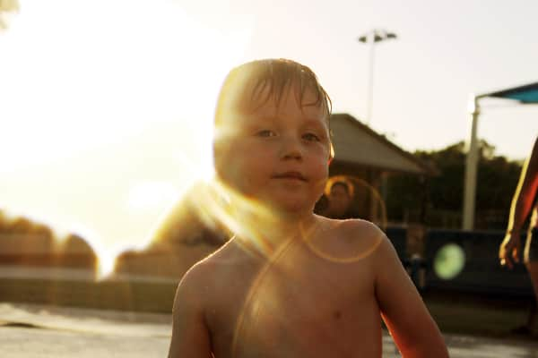 Little boy in the sunlight - swimming at the pool