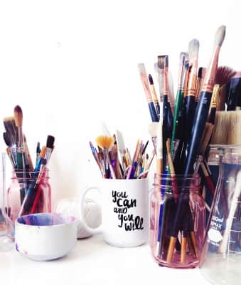 Collection of paintbrushes and art supplies organized in glass jars and coffee mugs with inspirational quote.