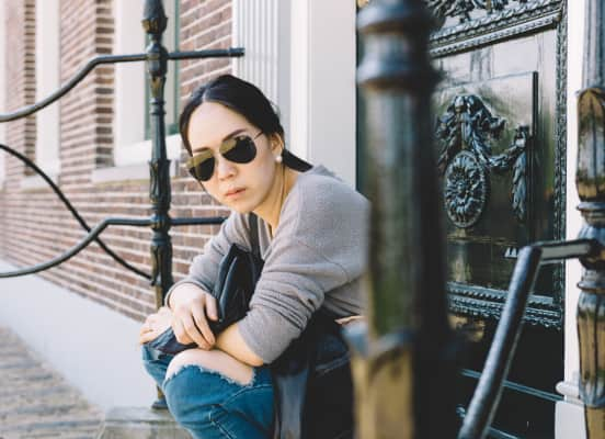 Woman in sunglasses sitting at front door