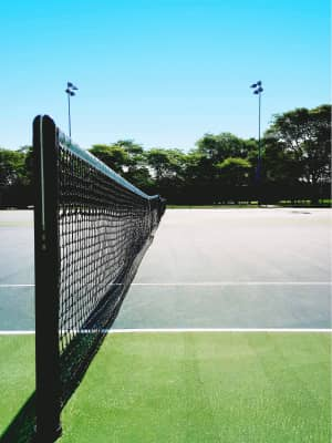 Taut nets on outdoor tennis courts under a clear blue sky.