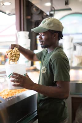 Man pouring popcorn into popcorn bucket for a customer
