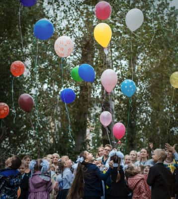 Children group launch balloons into the sky outdoors.
