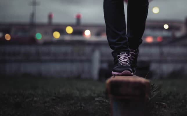 Female feet in the moody park on the night city background.