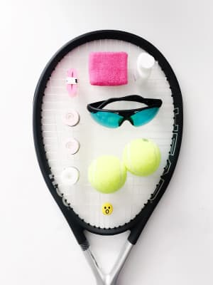 Head of tennis racquet with supplies arranged neatly on surface on a bright white background.
