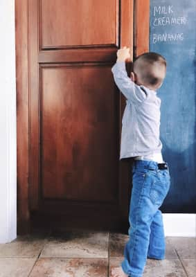 Young toddler boy standing in kitchen and peeking into wood pantry for a snack.