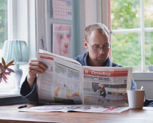 Man reading the newspaper and drinks coffee in the morning