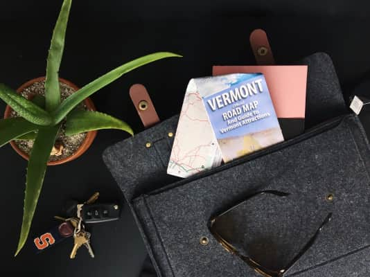 Vermont road map, bag and traveling accessories flat lay.