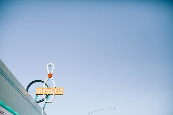 vintage, retro bowling alley sign sits in the sunny blue sky