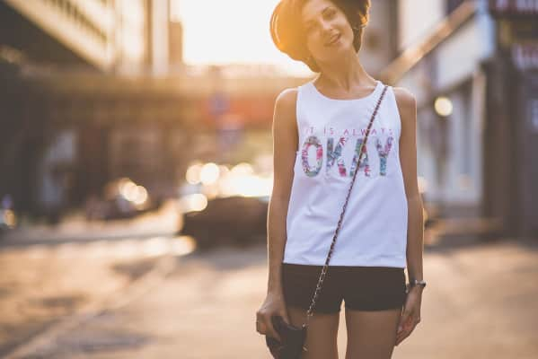 """Jumping smiling girl in t-shirt """"It is always okay"""""""