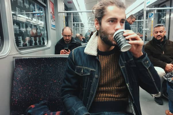 Young man drinking coffee in train
