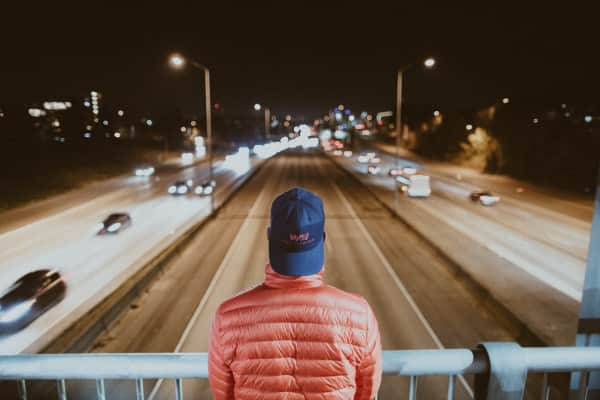 Man with backward hat looks out at a highway at night