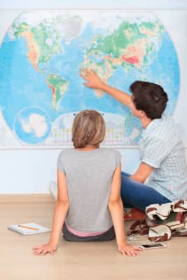 Boy and girl sitting by the map in classroom and learning together