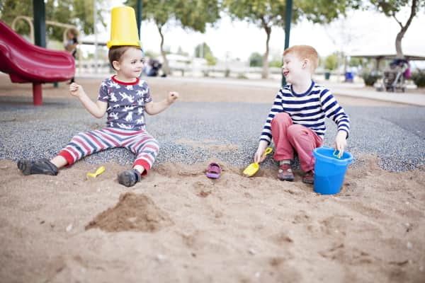 Boys playing with buckets and sand