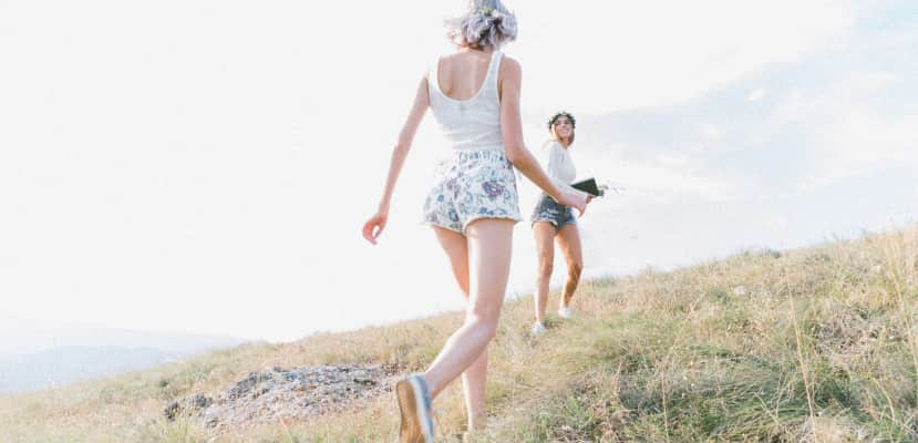Two young girls running on a meadow in the mountains