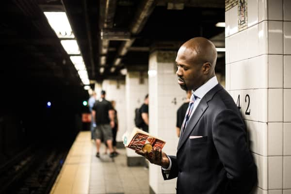 commute - man reading book at subway station