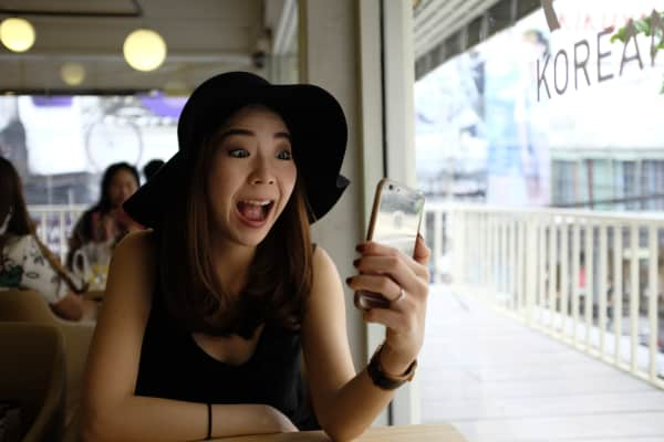 Asian woman taking selfie in cafe