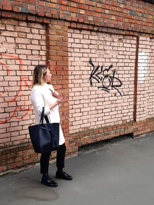 Fashionable woman in stylish clothes smoking an electronic cigarette and using mobile phone on pink brick wall background