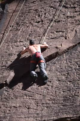 Serious climber on rock wall in the desert