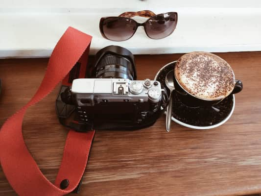 A camera, a cup of coffee and sunglass on wooden table