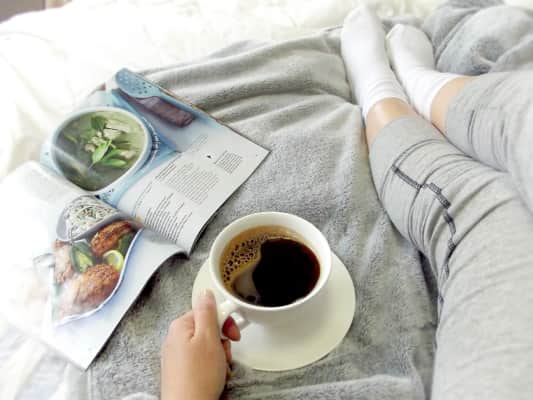 Relaxing in bed with coffee and a magazine