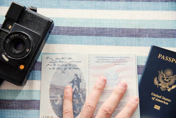 Close up overhead view of hand holding open a current US passport book with camera.