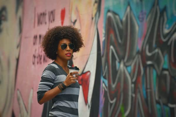 Drinking coffee in an alley surrounded by graffiti