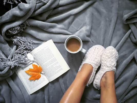 *NOMINATED* Flay lay of cozy fuzzy slippers with a book open and coffee on top of a cozy warm gray blanket.