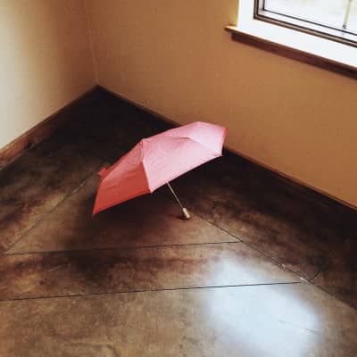 A pink umbrella lying on the floor next to a window. A pensive scene.