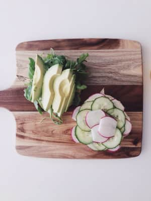 A vegetarian burger with cucumber, lettuce, radishes and avocado served on a wooden board.