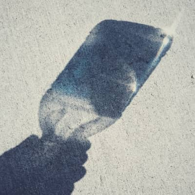 Shadow of a water-bottle reflecting on the pavement.