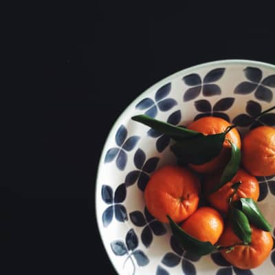Winter citrus - satsumas with leaves in bowl.