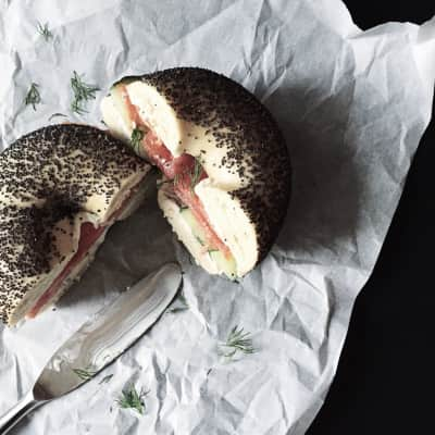 Smoked salmon, cucumber, dill, cream cheese between poppy seed bagel