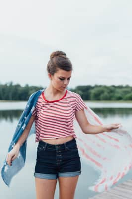 girl draped in American flag scarf standing on a dock.