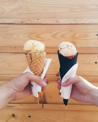 Two hands holding ice-creams in front of the wall