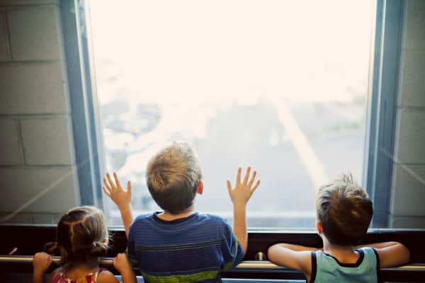 three kids look out of an elevator window