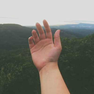 An outstretched hand over beautiful scenery: rolling hills, the city, and the sea.