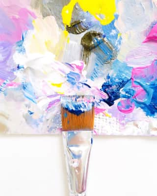 One single paintbrush mixing wet paint on a colorful painting palette.