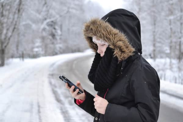 Girl with a smartphone and winter clothing