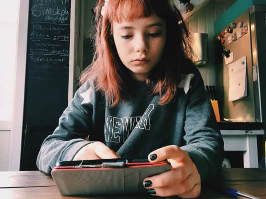 Girl using her phone in the kitchen