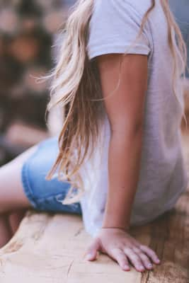 Little blonde sitting in the wooden bench