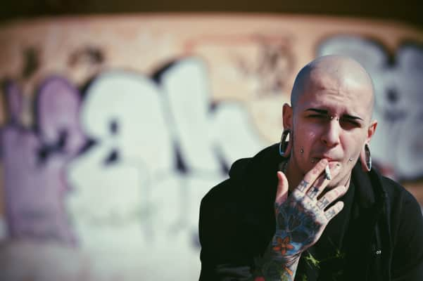 Alternative tattoed boy model with cigarette and bokeh background.