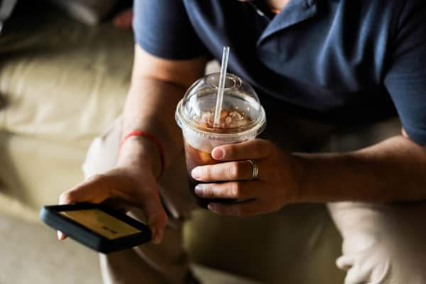 A man holds an iced coffee in one hand and a mobile phone on the other as he reads from it