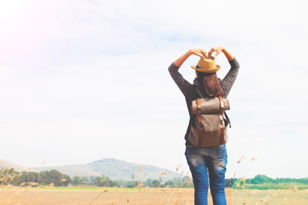 Happy woman traveler looking to blue sky and hands love sign, wanderlust travel concept, space for text